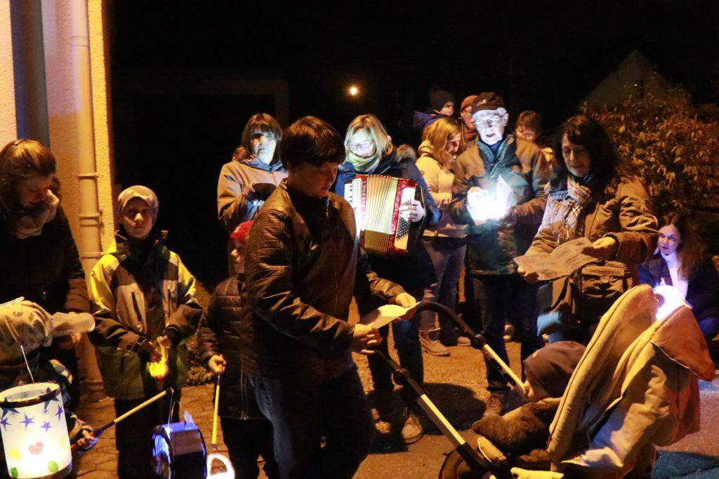 Kinder mit ihren Laternen, die zu Akkordeonmusik singen.