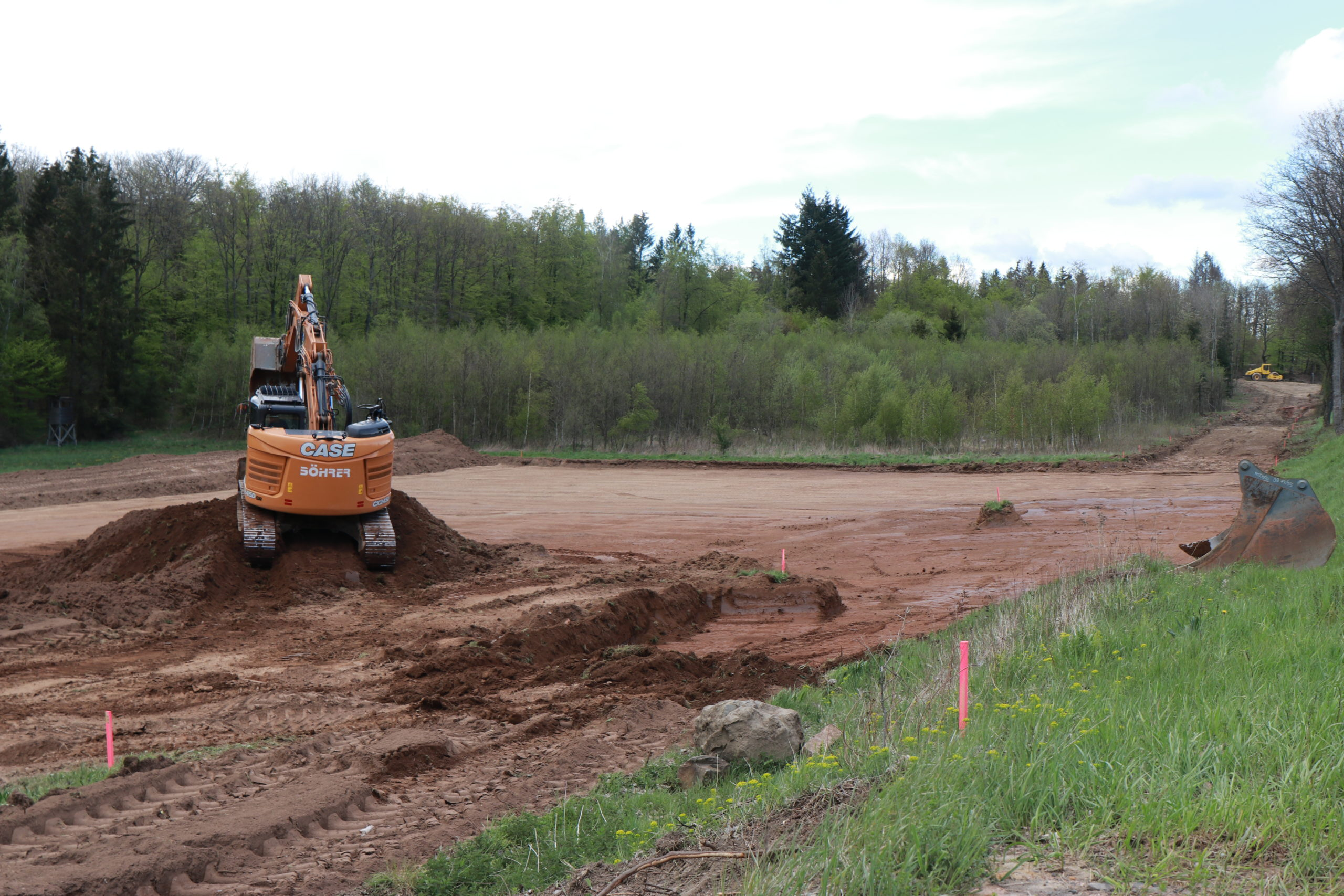 B41-Ausbau: Ein Bagger steht auf einem aufgeschütteten Haufen Erde in der Nähe der B41.