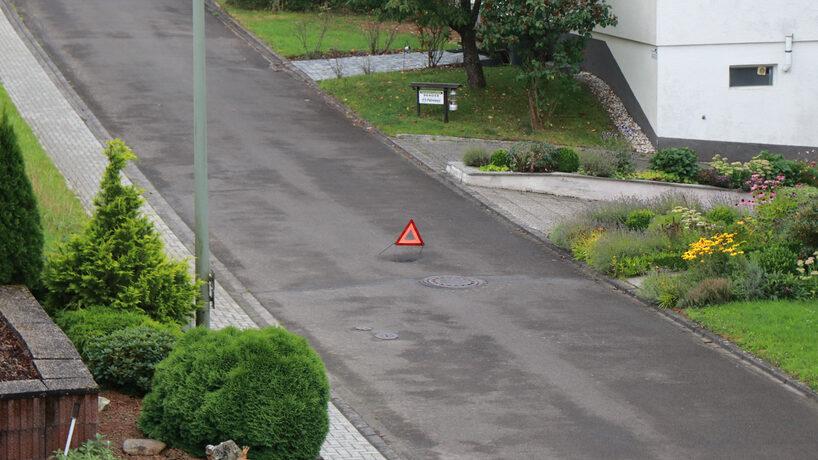 """Ein Warndreieck steht in der Straße """"Im Grünesfeld"""""""